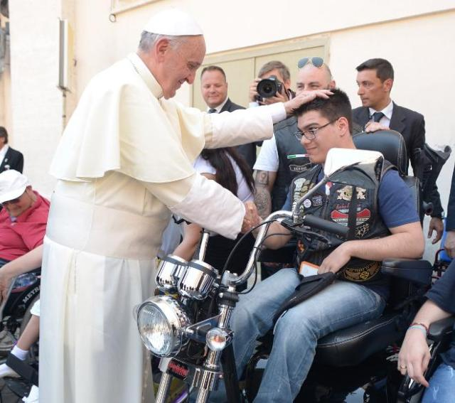 Pope Francis blesses a man at the end of Mass Sunday in St. Peter's Square at the Vatican. The pope blessed Harley-Davidson bikes and bikers as the Wisconsin motorcycle manufacturer celebrated its 110th anniversary with a parade and plenty of leather.