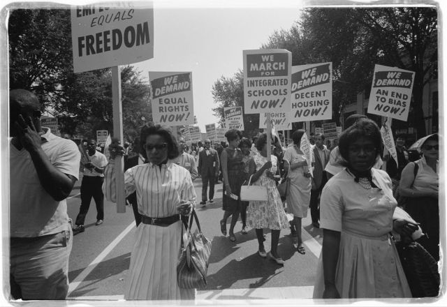A procession of African Americans carrying signs for equal rights, integrated schools, decent housing, and an end to bias on August 28, 1963. Photo courtesy U.S. Library of Congress