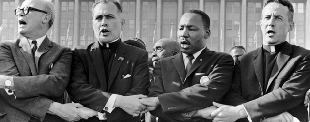 Martin Luther King, Jr. joining hands with Catholic clergy and other religious leaders.